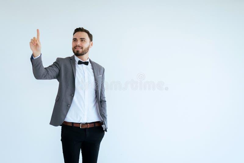 Красивый человек с бородатым в официальных смокинге и руке показа костюма указывая что-то на белой предпосылке, копирует космос д стоковое изображение