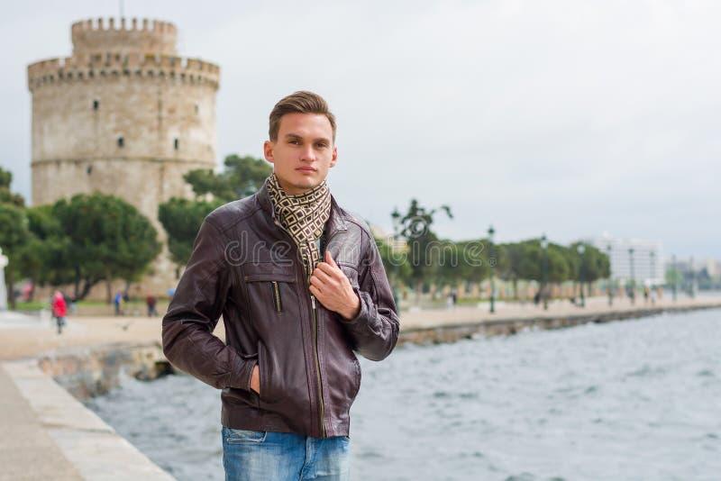 Красивый человек, туристский, стоит около белой башни в центре Thessaloniki, Греции перед морем стоковые изображения rf