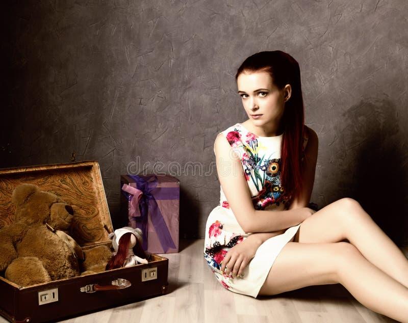 Красивый чемодан упаковки молодой женщины и получать готовый для путешествовать, ретро концепция стоковое фото rf
