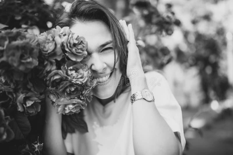 Красивый черно-белый портрет чувственной молодой женщины брюнет в белом платье близко к красным розам стоковое изображение rf