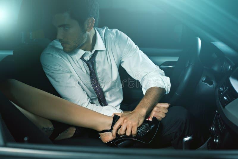 Красивый человек в автомобиле сокращанном ногой женщины стоковое фото rf