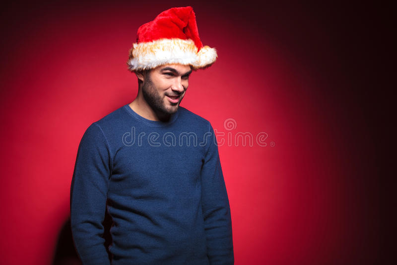 Красивый человек в голубом свитере нося красную шляпу santa стоковое фото