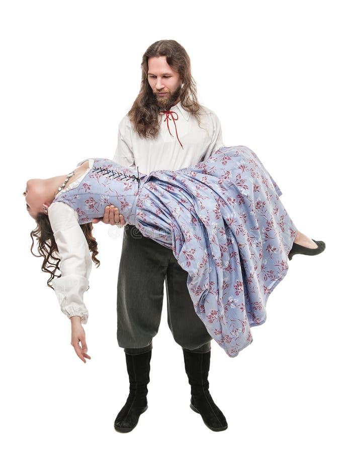 Красивый человек в средневековом костюме держа красивую женщину на его стоковая фотография rf