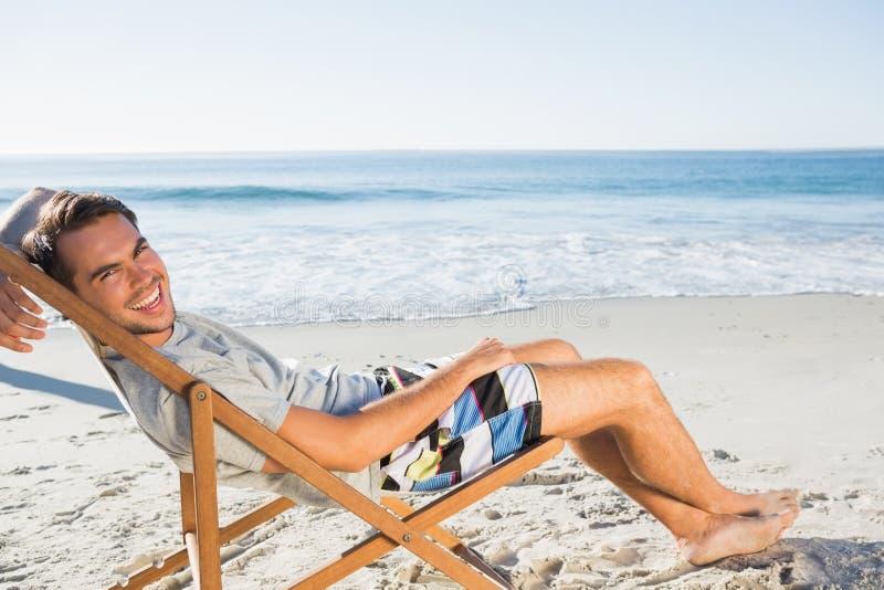 Красивый человек лежа на его шезлонге усмехаясь на камере стоковое изображение
