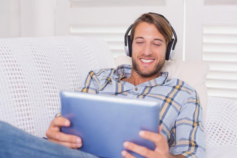 Красивый человек лежа на кресле слушая к музыке на ПК таблетки стоковые изображения rf