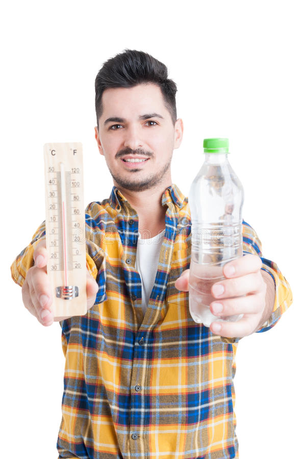 Красивый человек держа бутылку воды и термометра стоковое фото