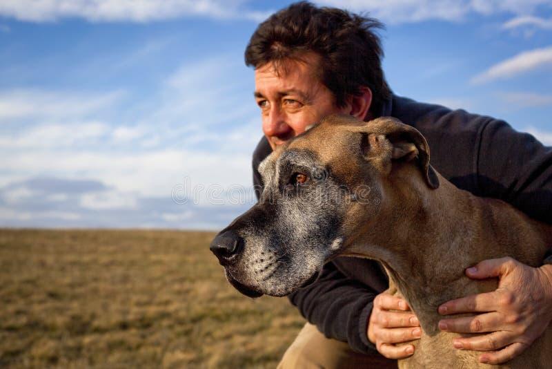 Красивый человек держа его собаку смотря в ветер стоковые фото