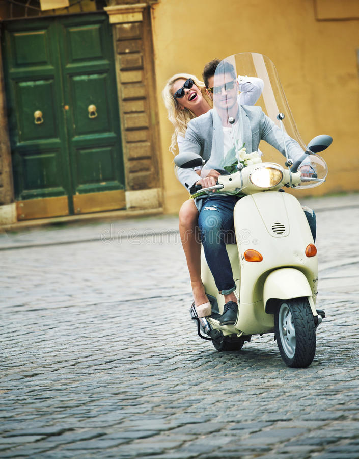 Красивый человек ехать самокат с его подругой стоковая фотография