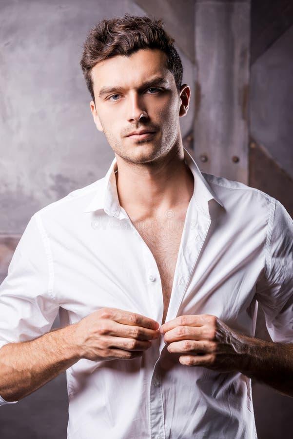 Красивый человек застегивая рубашку стоковое фото