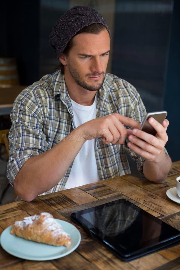 Красивый человек используя мобильный телефон на таблице в кофейне стоковые изображения rf