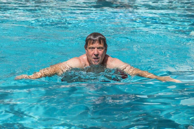 Красивый человек наслаждается поплавать в бассейне стоковое изображение rf