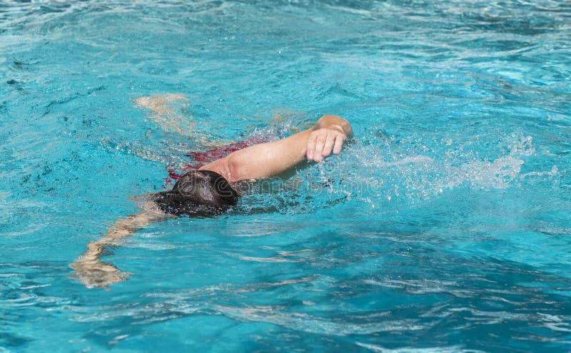 Красивый человек наслаждается поплавать в бассейне стоковые изображения