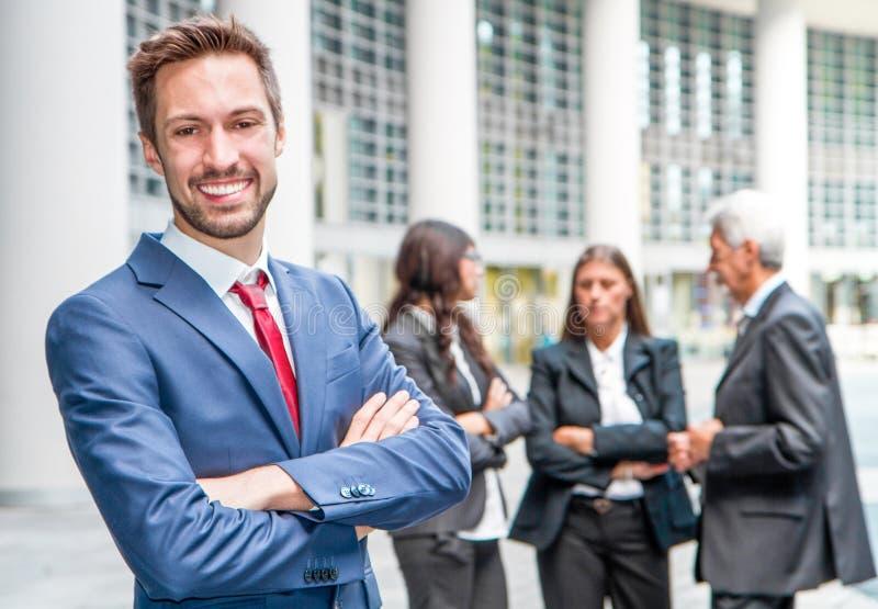 Красивый человек на предпосылке бизнесменов стоковое изображение rf