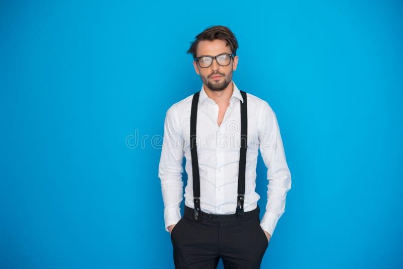Красивый человек на рубашке и расчалках сини нося белых стоковое изображение rf