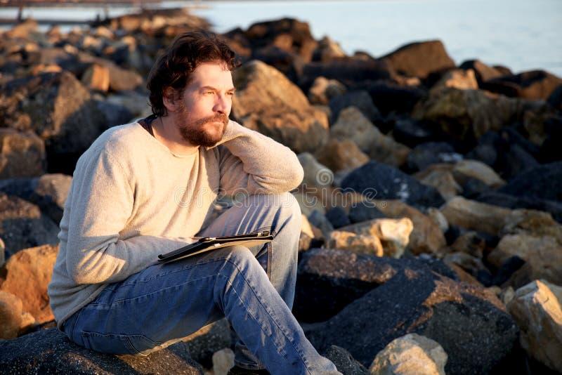Красивый человек ослабляя на пляже пока работающ с таблеткой во время захода солнца стоковая фотография rf