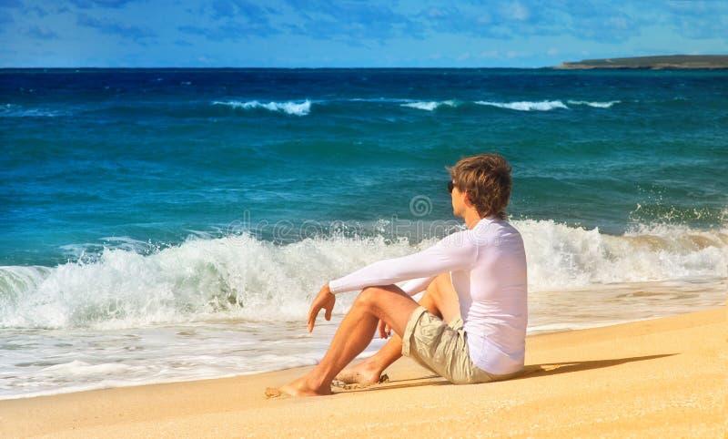 Красивый человек ослабляя на пляже сидя на песке взморья и смотря на временени волн моря стоковое фото