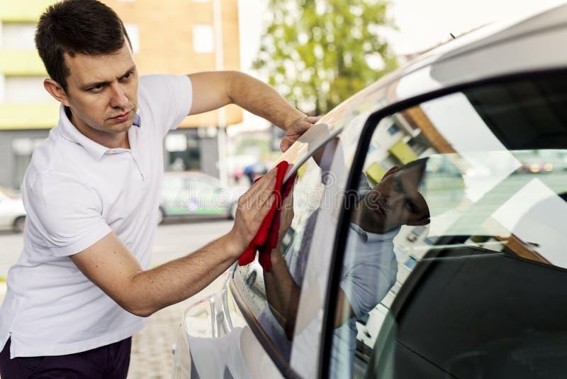 Красивый человек полируя его автомобиль стоковые изображения rf
