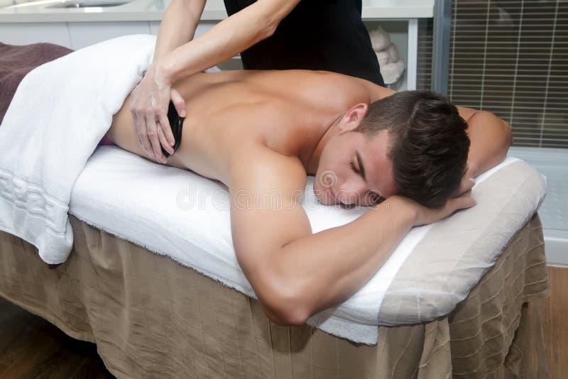 Красивый человек получая массаж с горячими камнями стоковое фото rf