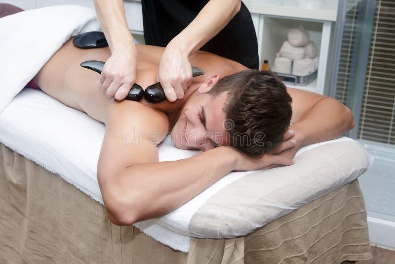 Красивый человек получая массаж с горячими камнями стоковое фото