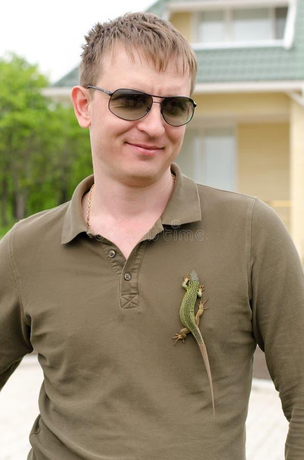 Красивый человек представляя с ящерицей на его рубашке стоковое фото