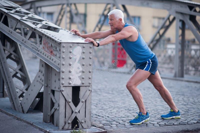 Красивый человек протягивая перед jogging стоковое изображение rf