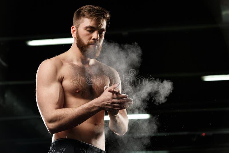 Красивый человек спорт в руках затирания спортзала с мелом стоковая фотография