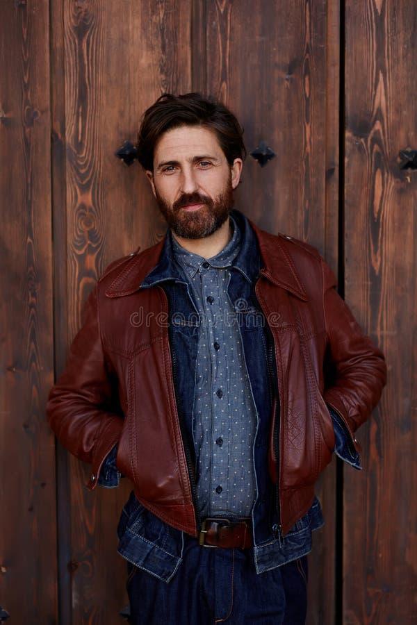 красивый человек стоит против фона деревянной загородки стоковые изображения