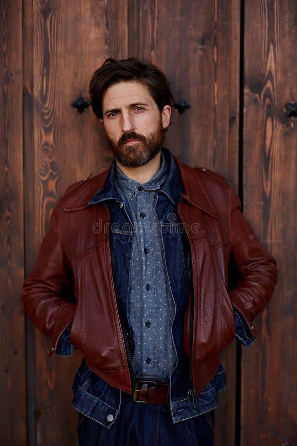 красивый человек стоя около коричневой двери стоковые изображения