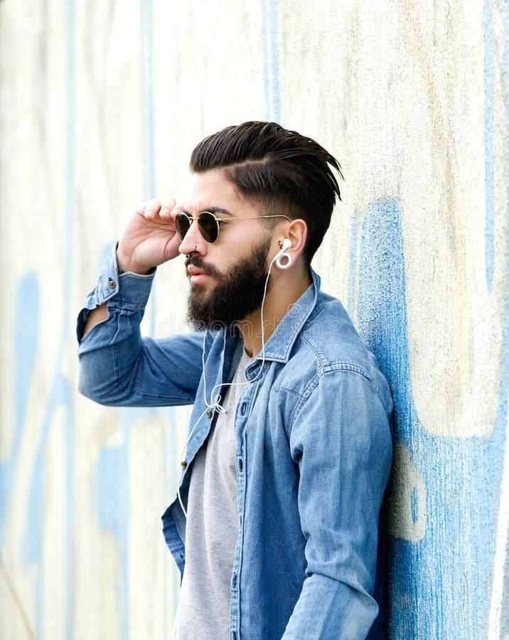 Красивый человек с бородой слушая к музыке с наушниками стоковые фото