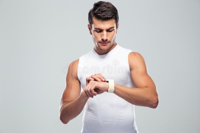Красивый человек фитнеса используя умный вахту стоковые фото