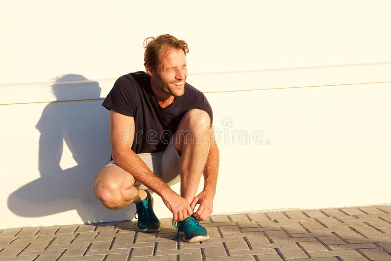 Красивый человек фитнеса усмехаясь и связывая шнурок стоковое изображение