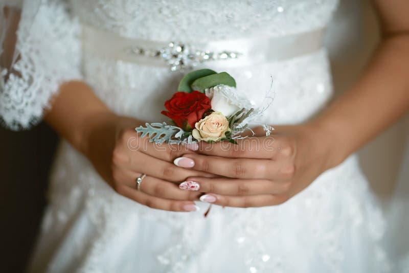 Красивый чувствительный букет свадьбы цветка и с белыми и красными цветками в руках ` s невесты в платье шнурка стоковые фото