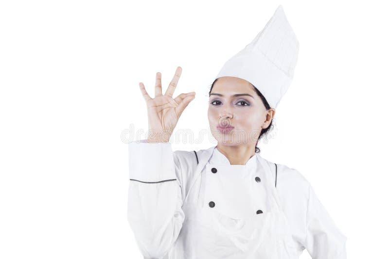 Красивый шеф-повар показывая ОДОБРЕННЫЙ знак на студии стоковые фотографии rf