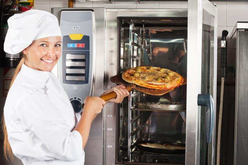 Красивый шеф-повар устанавливая пиццу в печи стоковые фото