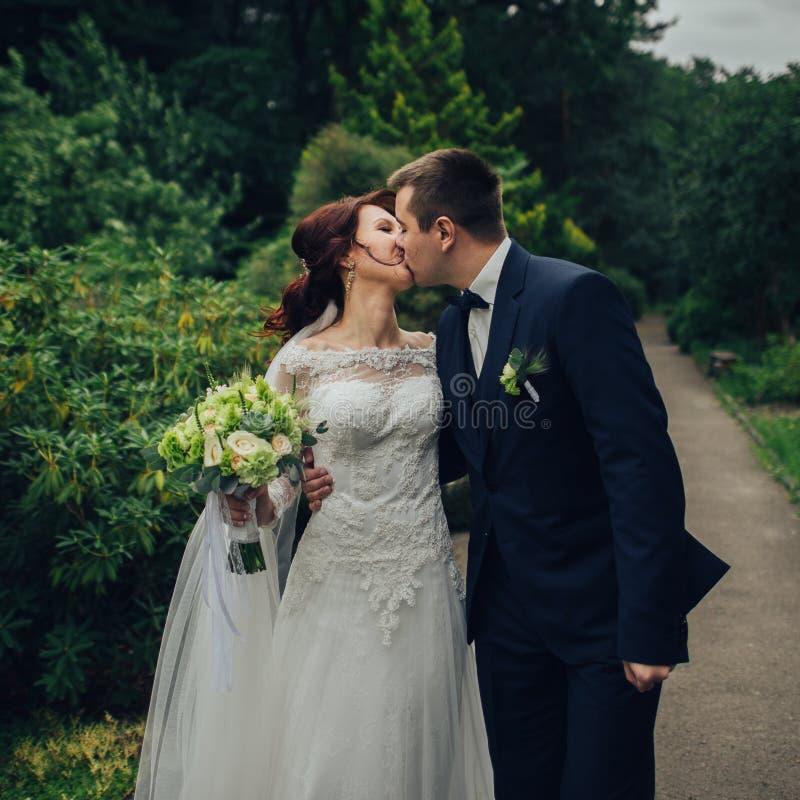 Красивый шикарный жених и невеста идя в солнечный парк и kis стоковые изображения rf