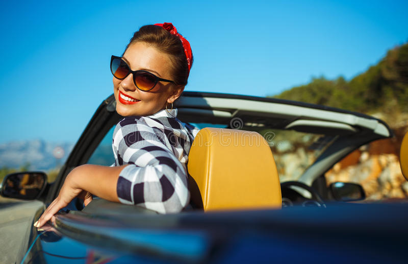 Красивый штырь вверх по женщине сидя в cabriolet, наслаждаясь отключением на lu стоковая фотография