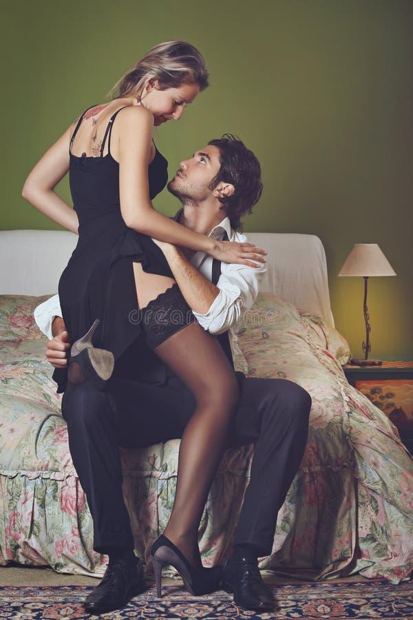 Красивый элегантный человек раздевая женщину стоковое изображение