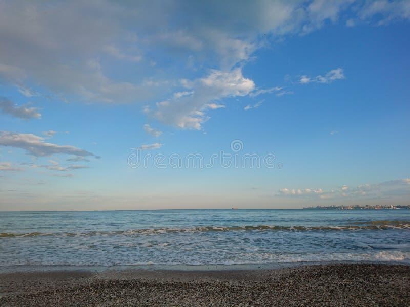 Красивый яркий голубой seascape: небо, облака, вода, волны, песок, ветер стоковая фотография rf
