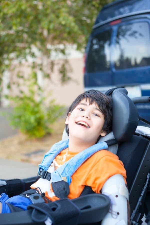 Красивый biracial неработающий мальчик в кресло-коляске, усмехаться внешний, r стоковая фотография rf
