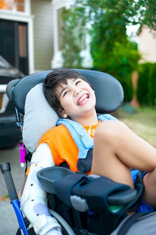 Красивый biracial неработающий мальчик в кресло-коляске, усмехаться внешний, r стоковое фото