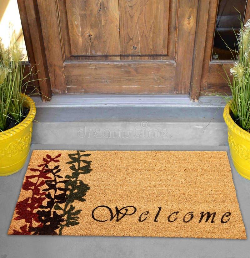 Красивый cursive радушный половик цвета персика с красным и черным заводом цветка помещенным вне двери с зелеными листьями стоковая фотография