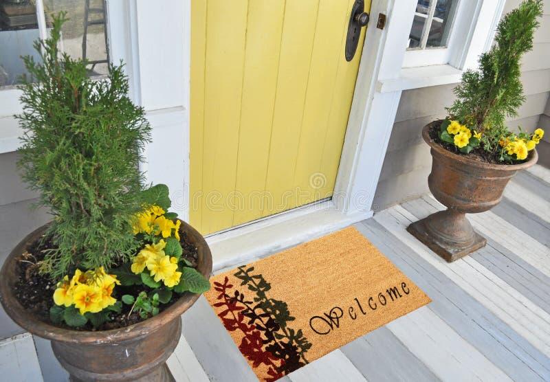 Красивый cursive радушный половик цвета персика с красным и черным заводом цветка помещенным вне двери с зелеными листьями стоковое фото rf
