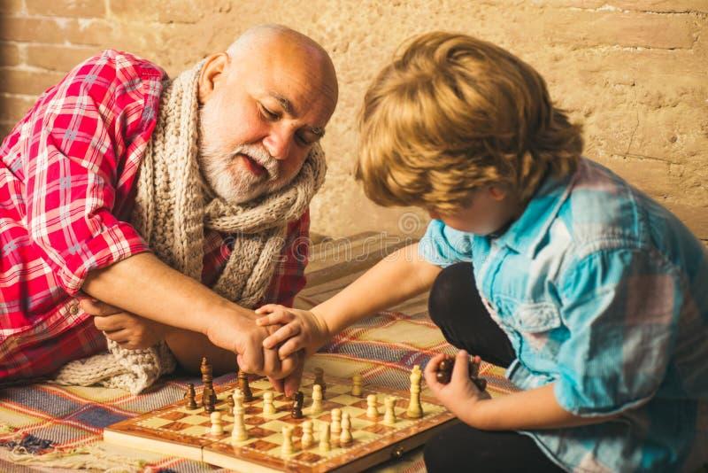Красивый grandpa и внук играют шахматы пока тратящ время совместно дома Хобби шахмат - дедушка с стоковое изображение
