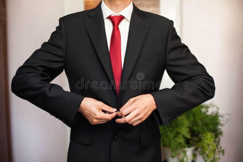 красивый groom в стильном костюме на комнате предпосылки стоковые фотографии rf