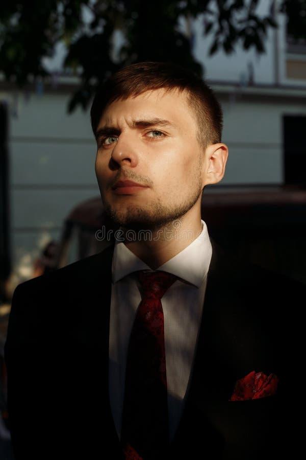Красивый groom в черном стильном костюме с красный представлять связи внешний стоковая фотография rf