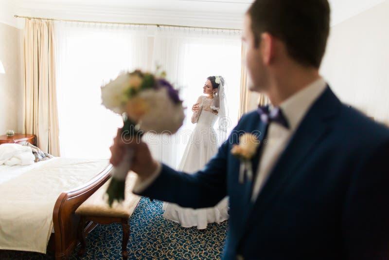 Красивый groom при букет представляя на красивой предпосылке невесты в гостиничном номере стоковое фото