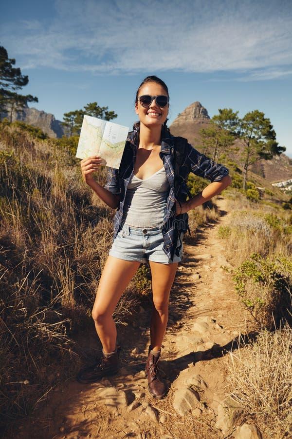 Красивый hiker женщины представляя с картой стоковая фотография