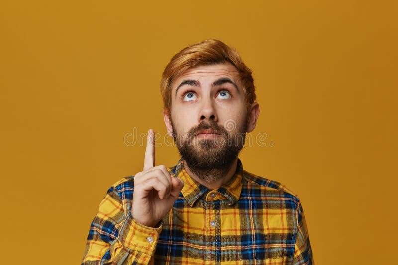 Красивый redhead покрасил бородатый мужской пункт с пальцем выше и смотрящ там серьезно стоковая фотография rf