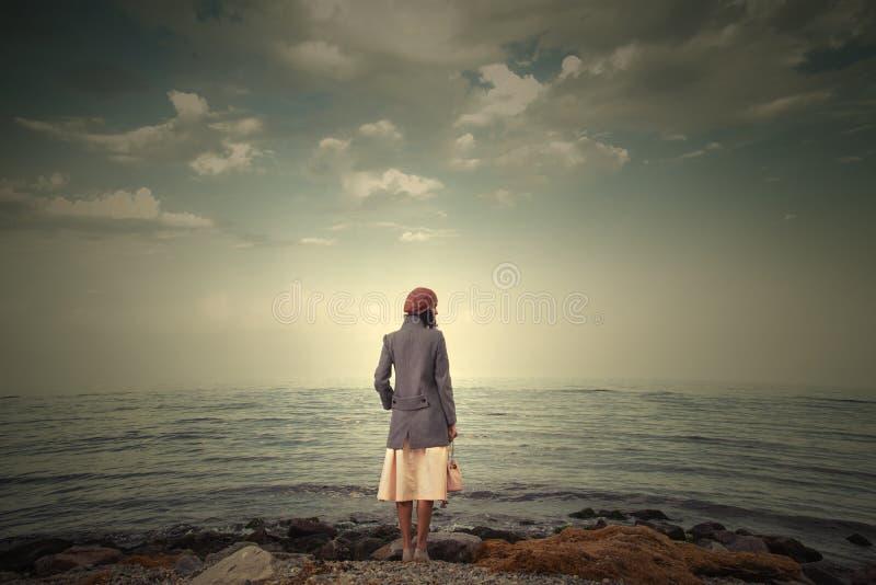 красивый seascape с ретро девушкой на береге стоковое изображение