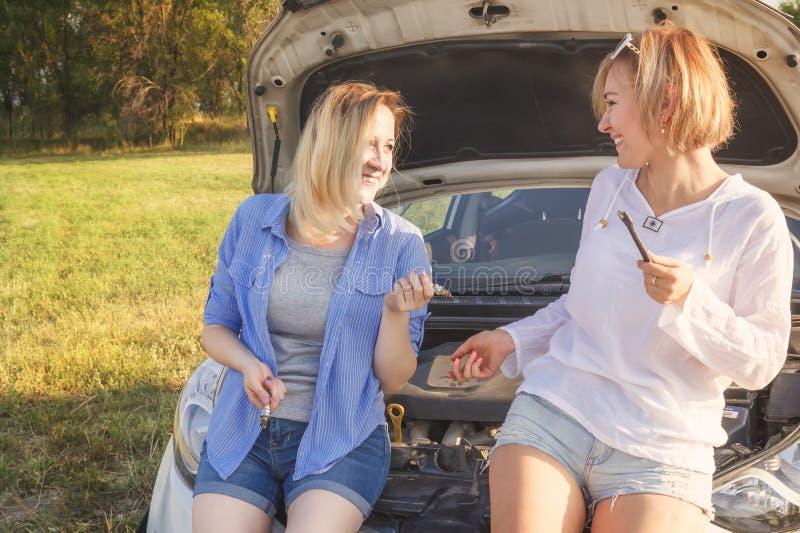 2 красивых белокурых девушки имеют потеху обсуждая ремонты автомобиля на проселочной дороге в лучах стоковая фотография rf